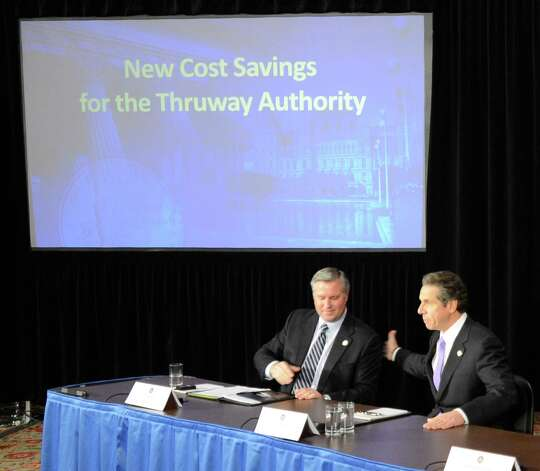 "Tom Madison, Director of the NYS Thruway Authority, left gives Governor Andrew Cuomo the details of the "" New Cost Savings"" for the Thruway Authority during a press conference  which was held in the Red Room of the State Capitol in Albany, N.Y. Dec 17, 2012.  (Skip Dickstein/Times Union) Photo: Skip Dickstein"