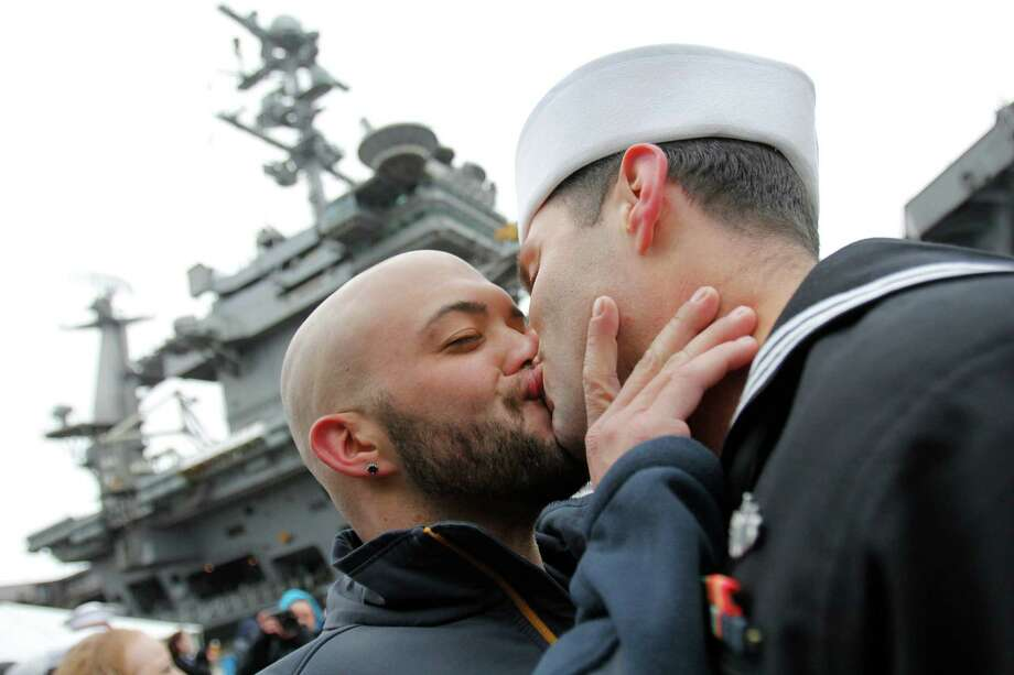 "March 2, 2012 — Sean Sutton, left, greets his boyfriend of 2 years, U.S. Navy sailor Jonathan Jewell, E5, with a kiss after Jewell returned from a seven month deployment aboard the USS John C. Stennis in Bremerton, Wash. The end of ""Don't Ask, Don't Tell"" in the U.S. military allowed same-sex couples to serve in the military without fear of being kicked out if their lifestyle was discovered. Photo: JOE DYER / SEATTLEPI.COM"