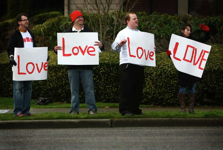 February 11, 2012 — From left, Dino Macioci, Joey Adams, Owen Anderson and Stacy Chan, all of Tacoma, hold signs outside the Life Center church in Tacoma after the funeral for Braden and Charlie Powell. The boys were killed by their father during a supervised visit near Graham, Wash. Photo: JOSHUA TRUJILLO / SEATTLEPI.COM