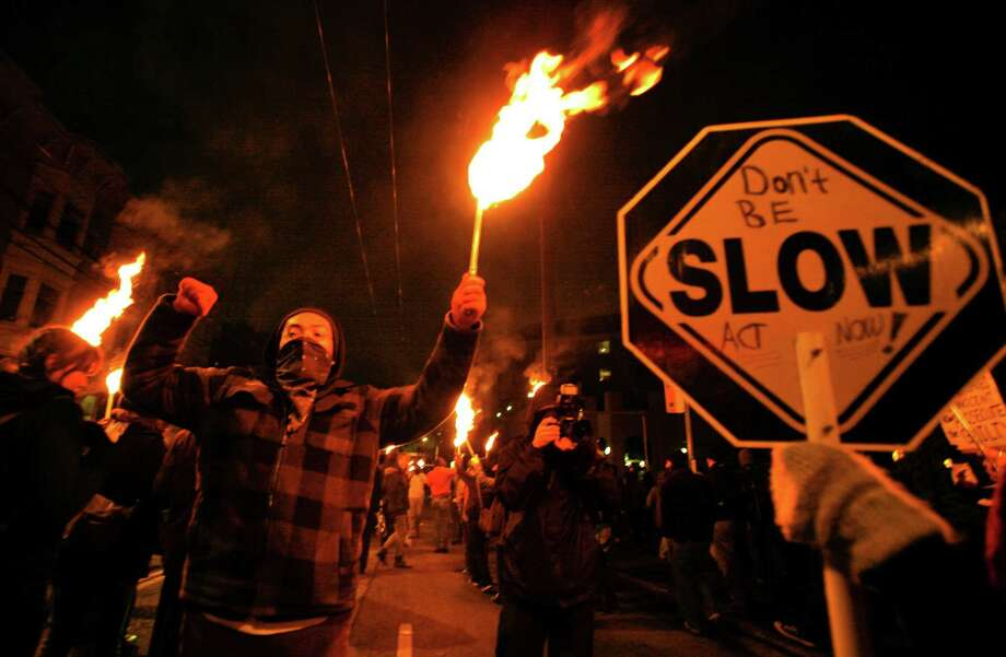 Jan. 14, 2012— Protesters carry lit torches to honor those killed by police as they near the east precinct. The protesters, who marched from 23rd and Union, called for the resignation of Chief John Diaz. Photo: LINDSEY WASSON / SEATTLEPI.COM