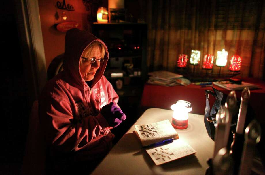 January 20, 2012— Doris Woodward warms her hands as she takes a break from a cross-word puzzle in Auburn. Power was out in her home and she was without heat. An ice storm wreaked havoc in the area, bringing down trees and power lines. Power was out in large parts of the area. Photo: JOSHUA TRUJILLO / SEATTLEPI.COM