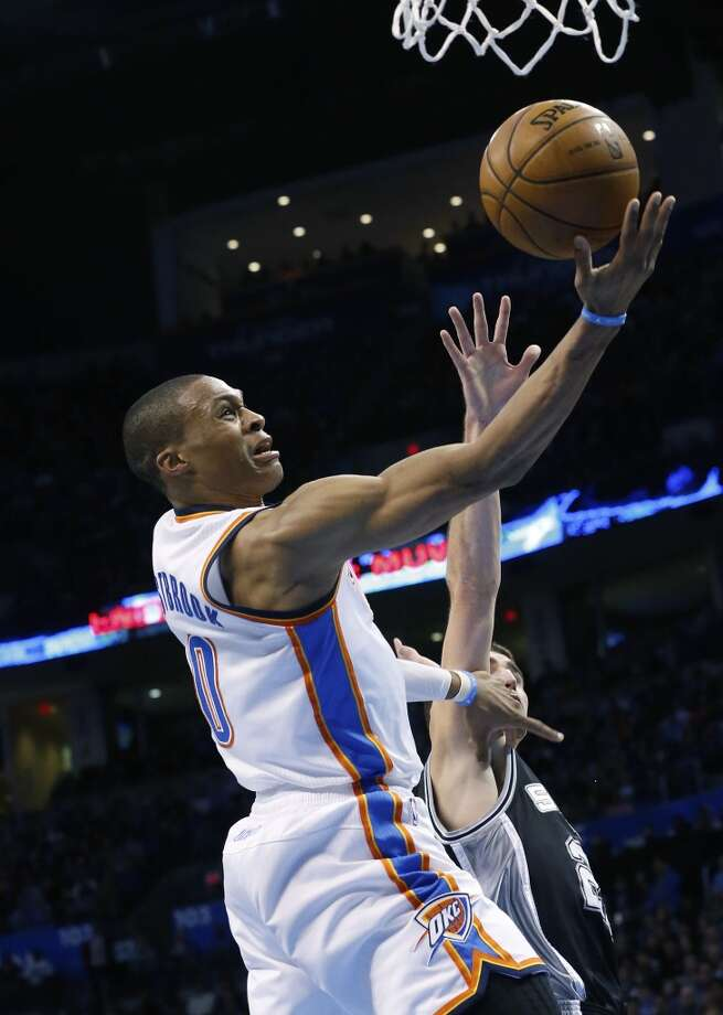 Oklahoma City Thunder guard Russell Westbrook (0) shoots in front of San Antonio Spurs guard Nando De Colo (25) in the second quarter of an NBA basketball game in Oklahoma City, Monday, Dec. 17, 2012.  (Sue Ogrocki / Associated Press)
