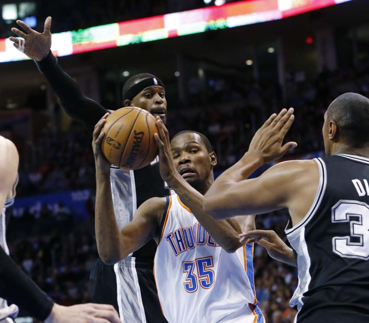 Oklahoma City Thunder forward Kevin Durant (35) drives between San Antonio Spurs guard Stephen Jackson (3) and forward Boris Diaw (33) in the second quarter of an NBA basketball game in Oklahoma City, Monday, Dec. 17, 2012. (Sue Ogrocki / Associated Press)
