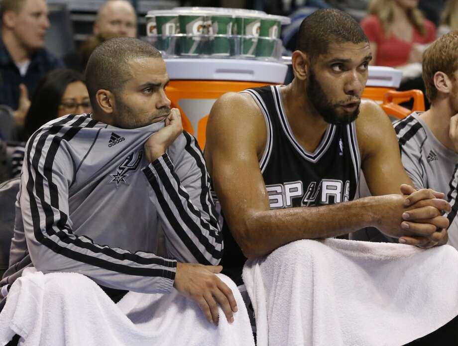 San Antonio Spurs guard Tony Parker, left, and forward Tim Duncan, right, watch from the bench in the fourth quarter of an NBA basketball game against the Oklahoma City Thunder in Oklahoma City, Monday, Dec. 17, 2012. Oklahoma City won 107-93.   (Sue Ogrocki / Associated Press)