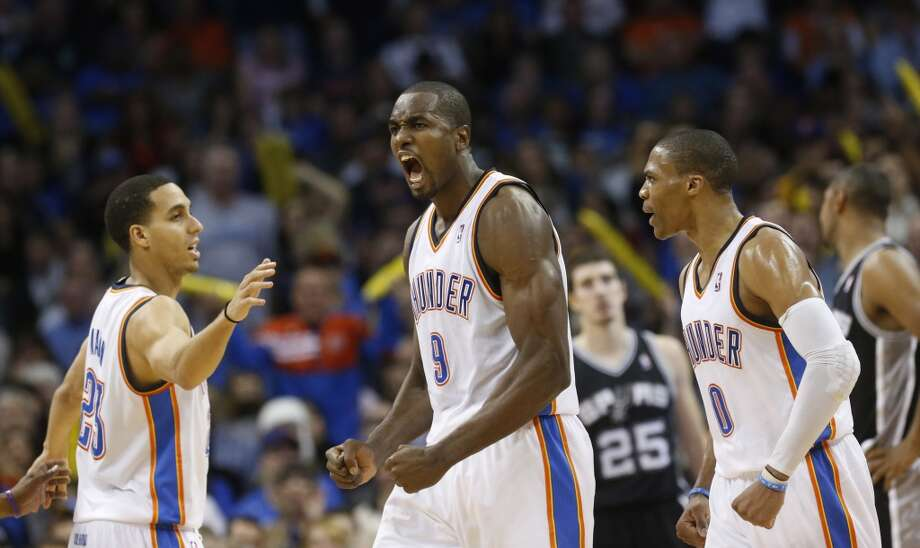 Oklahoma City Thunder forward Serge Ibaka (9) reacts after being fouled in the fourth quarter of an NBA basketball game against the San Antonio Spurs in Oklahoma City, Monday, Dec. 17, 2012. Oklahoma City Thunder guard Kevin Martin (23) is at left and Oklahoma City Thunder guard Russell Westbrook (0) is at right. Oklahoma City won 107-93.  (Sue Ogrocki / Associated Press)