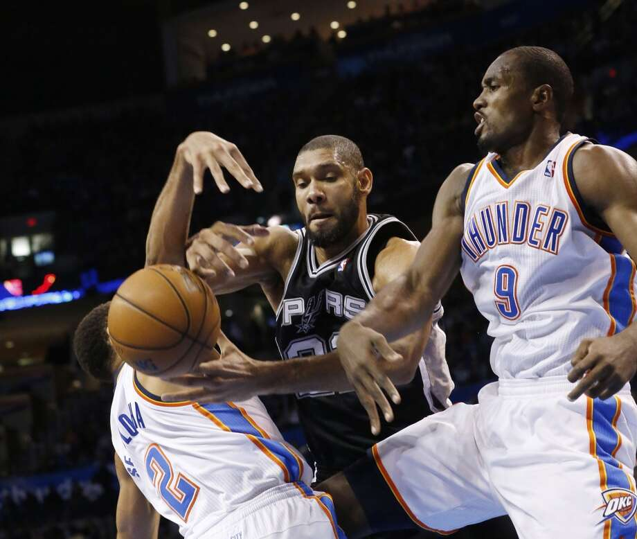 Oklahoma City Thunder guard Thabo Sefolosha (2)  and forward Serge Ibaka (9) knock the ball away from San Antonio Spurs forward Tim Duncan (21) in the third quarter of an NBA basketball game in Oklahoma City, Monday, Dec. 17, 2012. Oklahoma City won 107-93.  (Sue Ogrocki / Associated Press)