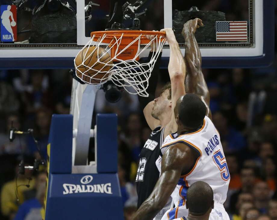 San Antonio Spurs center Tiago Splitter (22) dunks in front of Oklahoma City Thunder center Kendrick Perkins (5) in the first quarter of an NBA basketball game in Oklahoma City, Monday, Dec. 17, 2012. Oklahoma City won 107-93.  (Sue Ogrocki / Associated Press)