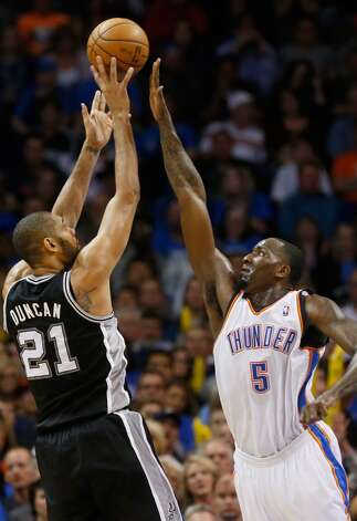 San Antonio Spurs forward Tim Duncan (21) shoots over Oklahoma City Thunder center Kendrick Perkins (5) in the first quarter of an NBA basketball game in Oklahoma City, Monday, Dec. 17, 2012. Oklahoma City won 107-93.  (Sue Ogrocki / Associated Press)