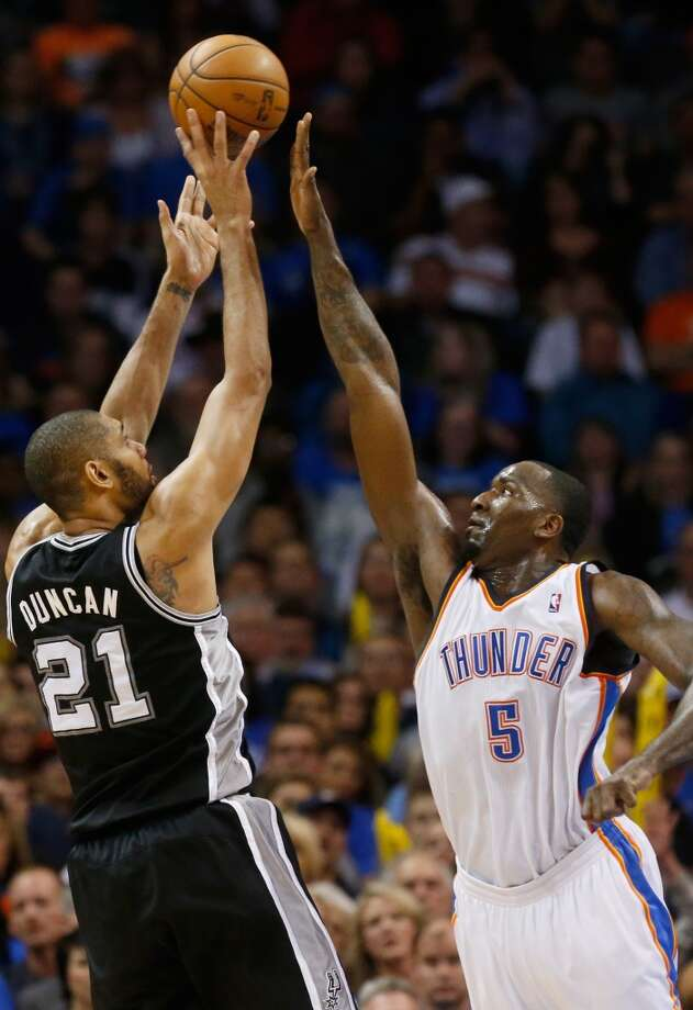 San Antonio Spurs forward Tim Duncan (21) shoots over Oklahoma City Thunder center Kendrick Perkins (5) in the first quarter of an NBA basketball game in Oklahoma City, Monday, Dec. 17, 2012. Oklahoma City won 107-93.  (Sue Ogrocki / Associated Press)