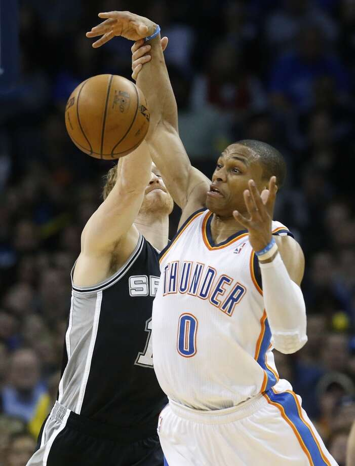 Oklahoma City Thunder guard Russell Westbrook (0) reaches for a loose ball in front of San Antonio Spurs forward Matt Bonner (15) in the first quarter of an NBA basketball game in Oklahoma City, Monday, Dec. 17, 2012. Oklahoma City won 107-93.  (Sue Ogrocki / Associated Press)