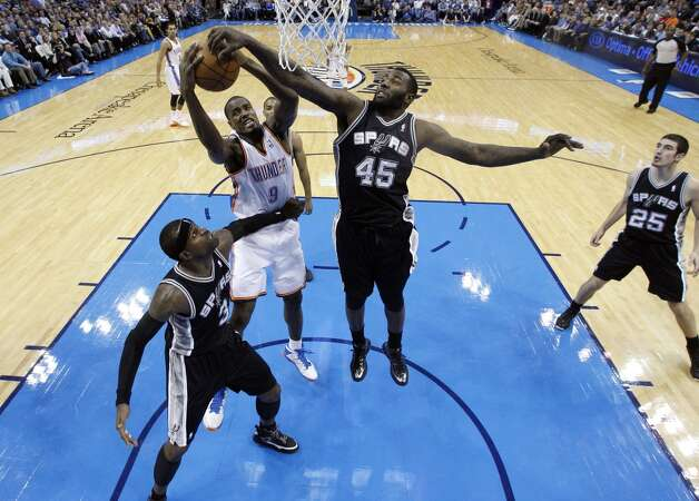 Oklahoma City Thunder forward Serge Ibaka (9) grabs a rebound between San Antonio Spurs center DeJuan Blair (45) and San Antonio Spurs guard Stephen Jackson (3) in the fourth quarter of an NBA basketball game in Oklahoma City, Monday, Dec. 17, 2012. Oklahoma City won 107-93.  (Sue Ogrocki / Associated Press)