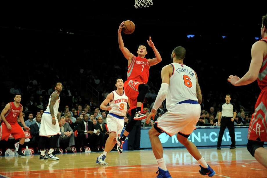 Jeremy Lin splits the Knicks' Pablo Prigioni, left, and Tyson Chandler while scoring two of his 22 points Monday night. The Rockets guard also had eight assists. Photo: Henny Ray Abrams, FRE / FR151332 AP
