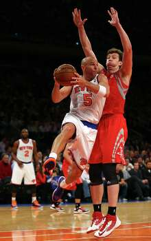 NEW YORK, NY - DECEMBER 17:  Jason Kidd #5 of the New York Knicks passes the ball as Omer Asik #3 of the Houston Rockets defends on December 17, 2012 at Madison Square Garden in New York City. The Houston Rockets defeated the New York Knicks 109-96. NOTE TO USER: User expressly acknowledges and agrees that, by downloading and/or using this photograph, user is consenting to the terms and conditions of the Getty Images License Agreement. Photo: Elsa, Getty Images / 2012 Getty Images