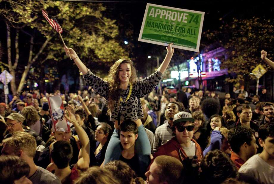 November 6, 2012 — Seattle University student Victoria Czorny rides on the shoulders of a friend as a spontaneous party erupts in the intersection of East Pike Street and 10th Avenue as results come in showing Referendum 74 passing in the polls and a measure to legalize marijuana also was passing. The crowd also came out to celebrate as Barack Obama was announced as the winner in the presidential race. Photo: JOSHUA TRUJILLO / SEATTLEPI.COM