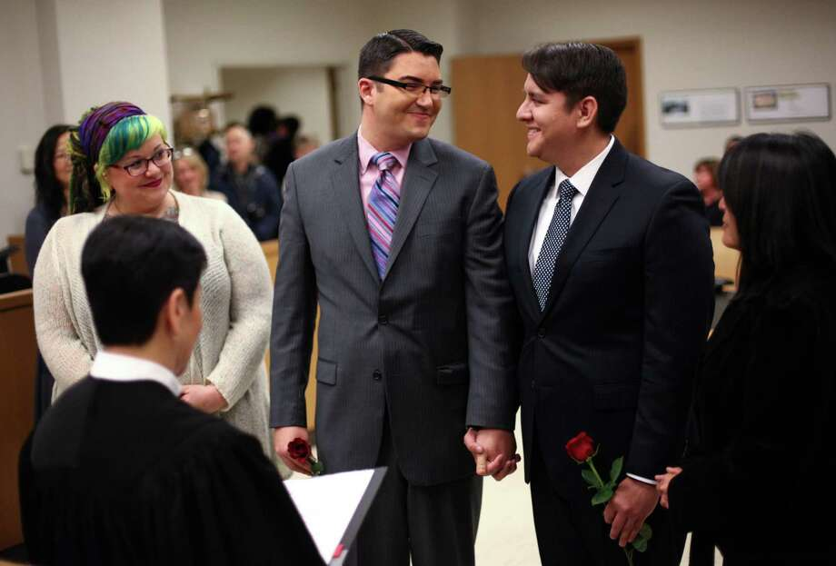 December 9, 2012— Jesse Page, left, and Brendan Taga, exchange wedding vows just after midnight at the King County Courthouse in Seattle. Marriage ceremonies were held in the courtroom of Superior Court Judge Mary Yu beginning at 12:01 a.m. on December 9, 2012, the first day same-sex couples in Washington State could legally be married. Photo: JOSHUA TRUJILLO / SEATTLEPI.COM