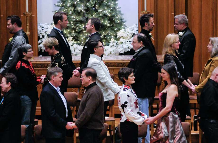 December 9, 2012 — Couples hold hands as they prepare to exchange vows and rings during a Service of Marriage at the First Baptist Church on Capitol Hill. 25 same-sex couples were wed in a historic celebration on the first day they were legally allowed to marry in Washington State. Photo: LINDSEY WASSON / SEATTLEPI.COM