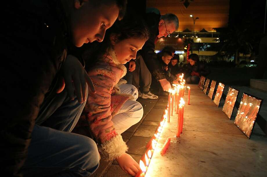 Albanian children light candles as pay their respects at Tirana's main square on December 17, 2012, to the victims of a elementary school shooting in Newtown, Connecticut. Photo: Gent Shkullaku, AFP/Getty Images