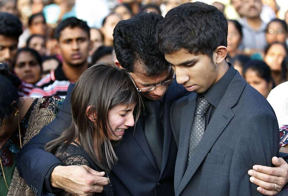 Husband Benedict Barboza, center, holds his son Junal, right, and daughter Lisha during the burial of nurse Jacintha Saldanha at her hometown Shirva, near Mangalore in southwest India, Monday, Dec. 17, 2012. Nurse Saldanha was found hanging in her room days after she had been duped by a hoax call from an Australian radio station about the pregnant Duchess of Cambridge. Photo: Rafiq Maqbool, Associated Press