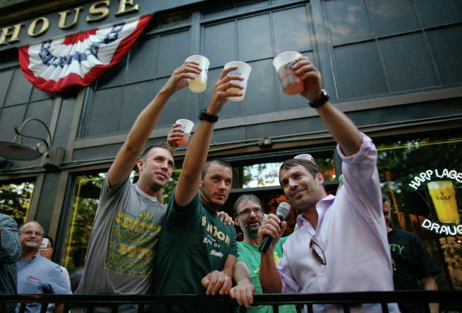 September 13 ,2012— Ricky Oliver, left, and Colin Hughes join arena investor Chris Hansen, right, during a toast at FX McRory's in the Pioneer Square neighborhood. Seattle arena investor Chris Hansen bought a round of beers for hundreds of arena supporters after the Seattle City Council voted to approve an arena proposal. Photo: JOSHUA TRUJILLO / SEATTLEPI.COM
