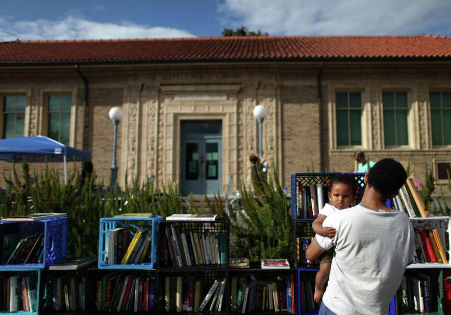"""August 28, 2012— Sena Berhane holds his son Samuel Sena, 8-months, as he browses books at """"The People's Library"""" set up in front of the Douglass-Truth branch of the Seattle Public Library in the Central District. Seattle Public Libraries closed during a weeklong furlough, part of measures to trim from the library budget. During the closure a library popped up in front of the building with books donated by community members. Photo: JOSHUA TRUJILLO / SEATTLEPI.COM"""