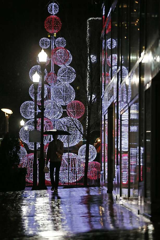 With temperatures in the 50's and rain all day a Pittsburgher walks past a Christmas display in Market Square in downtown Pittsburgh Monday, Dec. 17, 2012. Photo: Gene J. Puskar, Associated Press