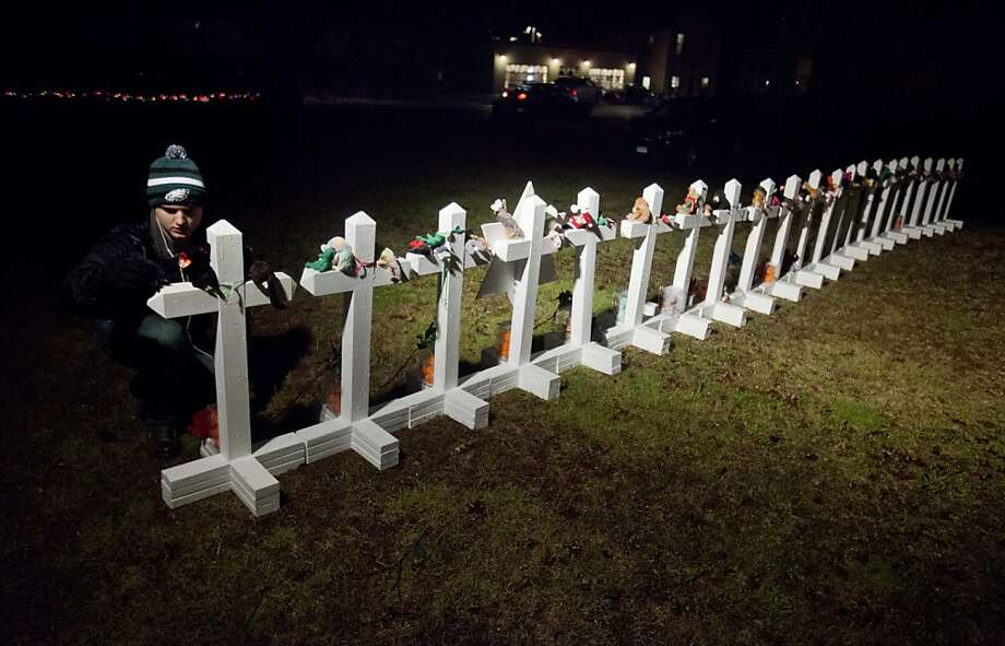 Frank Kulick, adjusts a display of wooden crosses, and a Jewish Star of David, representing the victims of the Sandy Hook Elementary School shooting, on his front lawn, Monday, Dec. 17, 2012, in Newtown, Conn. (AP Photo/David Goldman) Photo: David Goldman, Associated Press