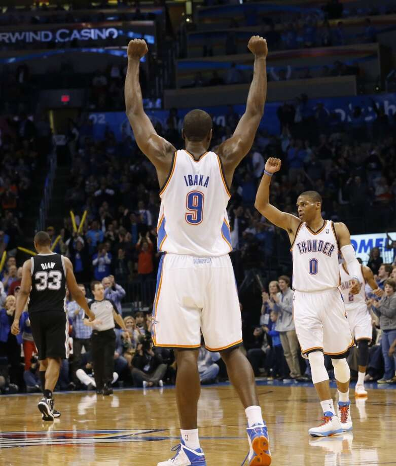 Oklahoma City Thunder forward Serge Ibaka (9) and guard Russell Westbrook (0) react to a basket against the San Antonio Spurs during an NBA basketball game in Oklahoma City, Monday, Dec. 17, 2012. Oklahoma City won 107-93. (Sue Ogrocki / Associated Press)