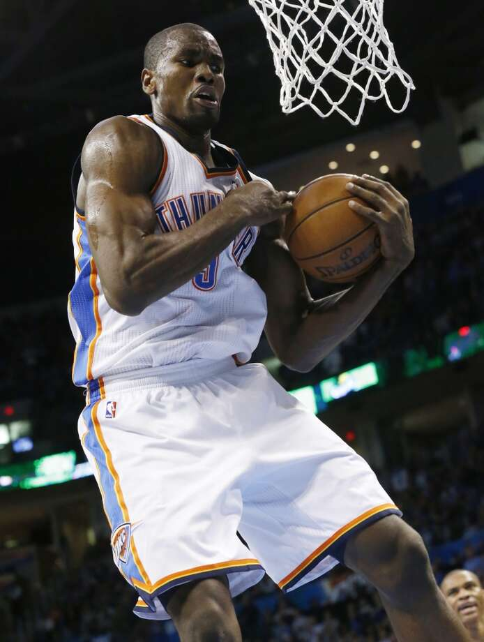Oklahoma City Thunder forward Serge Ibaka (9) grabs a rebound against the San Antonio Spurs during an NBA basketball game in Oklahoma City, Monday, Dec. 17, 2012. Oklahoma City won 107-93.  (Sue Ogrocki / Associated Press)