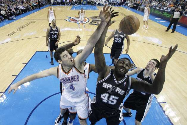 Oklahoma City Thunder forward Nick Collison (4) and San Antonio Spurs center DeJuan Blair (45) reach for a rebound during an NBA basketball game in Oklahoma City, Monday, Dec. 17, 2012. Oklahoma City won 107-93.  (Sue Ogrocki / Associated Press)