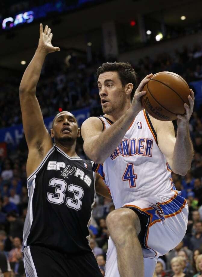 Oklahoma City Thunder forward Nick Collison (4) drives past San Antonio Spurs forward Boris Diaw (33) during an NBA basketball game in Oklahoma City, Monday, Dec. 17, 2012. (Sue Ogrocki / Associated Press )