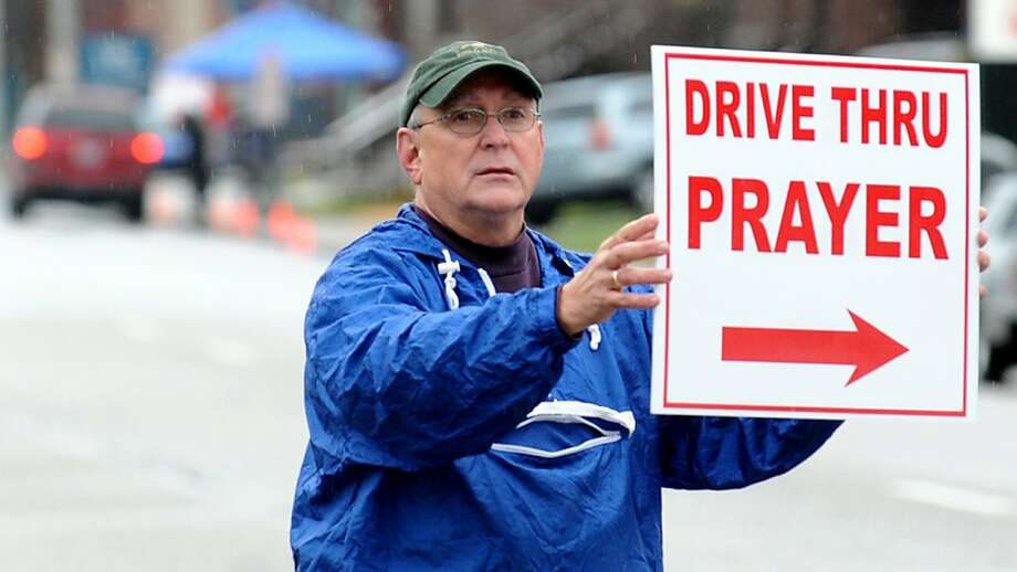 Bob Owen stands in the rain holding out a sign directing motorists along Carter Avenue in Ashland, Ky. to the drive-thru prayer service hosted by First United Methodist Church Monday Dec. 17, 2012. Photo: Kevin Goldy, Associated Press
