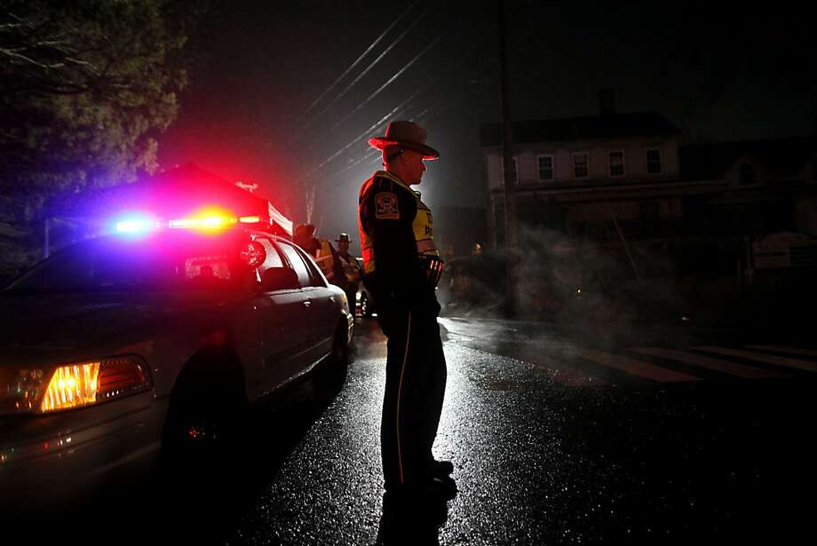 A Connecticut state trooper mans a checkpoint on the road leading towards Sandy Hook Elementary School, Monday, Dec. 17, 2012, in Newtown, Conn. A gunman walked into Sandy Hook Elementary School in Newtown Friday and opened fire, killing 26 people, including 20 children. (AP Photo/Jason DeCrow) Photo: Jason DeCrow, Associated Press