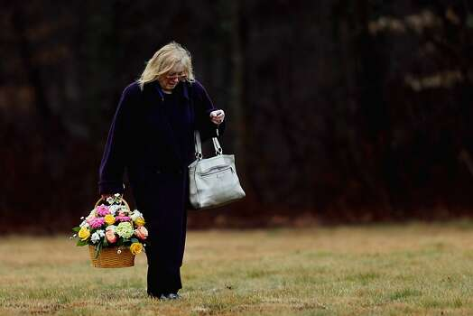 MONROE, CT - DECEMBER 17:  A woman carries a basket of flowers at the funeral services for six year-old Noah Pozner, who was  killed in the shooting massacre in Newtown, CT, at B'nai Israel Cemetery on December 17, 2012 in Monroe, Connecticut. Today is the first day of funerals for some of the twenty children and seven adults who were killed by 20-year-old Adam Lanza on December 14, 2012.  (Photo by Spencer Platt/Getty Images) Photo: Spencer Platt, Getty Images