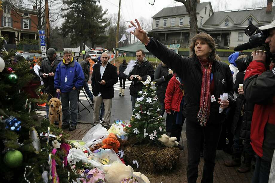Mylene Poitras tosses white feathers over a makeshift memorial on Monday, December 17, 2012, in Newtown, Connecticut. Poitras, a hospice expressive art specialist, met with survivors from Sandy Hook Elementary School. The white feathers represent angel wings, Poitras said. (Cloe Poisson/Hartford Courant/MCT) Photo: Cloe Poisson, McClatchy-Tribune News Service