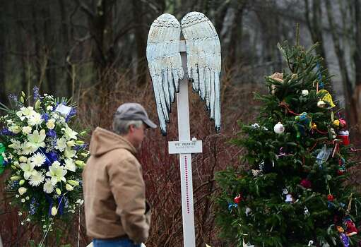 A man walks by a makeshift shrine to the victims of an elementary school shooting in Newtown, Connecticut, December 17, 2012. Funerals began Monday in the little Connecticut town of Newtown after the school massacre that took the lives of 20 small children and six staff, triggering new momentum for a change to America's gun culture. The first burials, held under raw, wet skies, were for two six-year-old boys who were among those shot in Sandy Hook Elementary School. On Tuesday, the first of the girls, also aged six, was due to be laid to rest. There were no Monday classes at all across Newtown, and the blood-soaked elementary school was to remain a closed crime scene indefinitely, authorities said. AFP PHOTO/Emmanuel DUNAND EMMANUEL DUNAND/AFP/Getty Images Photo: Emmanuel Dunand, AFP/Getty Images