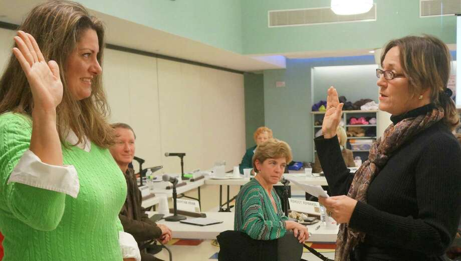 Jeannie Smith, left, is sworn in as a Board of Education member by Town Clerk Patricia Strauss at Monday's board meeting. Smith was appointed to fill the seat vacated by Jim Marpe.  Westport CT 12/17/12 Photo: Paul Schott / Westport News
