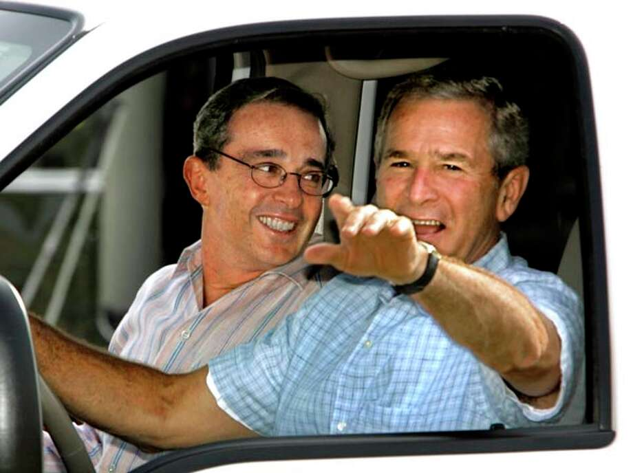 U.S. President George W. Bush welcomes Colombia's President Alvaro Uribe, left, with a drive in his pickup truck at his ranch in Crawford, Texas, Thursday, Aug. 4, 2005. Drug trafficking, terrorism and trade topped the agenda for the meeting at the ranch where Bush likes to conduct homespun diplomacy away from the formality of Washington. Photo: J. SCOTT APPLEWHITE, AP / AP
