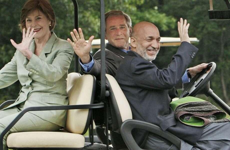 President Bush drives Afghan President Hamid Karzai and first lady Laura Bush in a golf cart at Camp David. (Charles Dharapak / AP Photo)