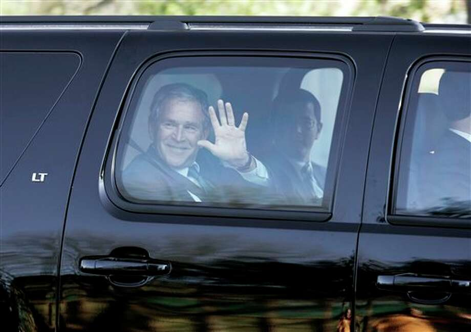 Former President George W. Bush waves to a jogger as he drives by on the way to his new residence in Dallas, Friday, Feb. 20,  2009. A month after leaving the White House, former President George W. Bush and his wife, Laura, moved into their new Dallas home Friday. Photo: Tony Gutierrez, AP / AP