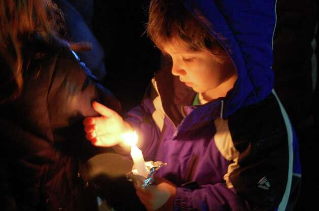 The child was among a crowd of about 200 people who came to a vigil Sunday evening in memory of the Sandy Hook School shooting victims, which took place at the site of the former Stratfield IGA Market. Fairfield CT 12/16/12 Photo: Jarret Liotta / Fairfield Citizen contributed