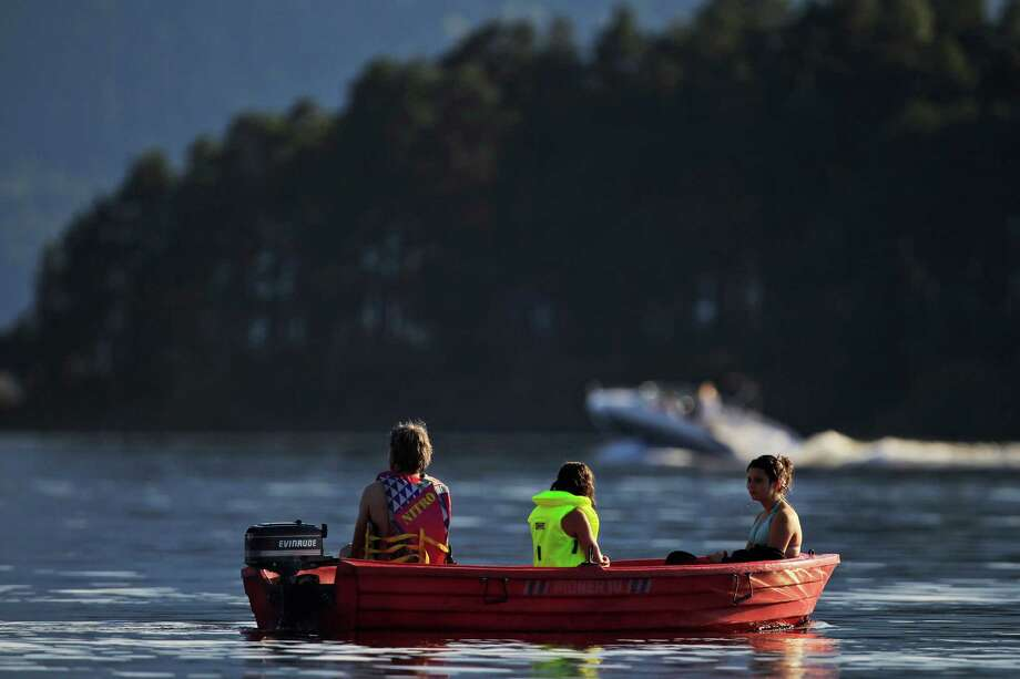 Young people enjoy a boat ride at the Tyrifjorden lake in Sundvollen, close to Utoya island, background, where gunman Anders Behring Breivik killed more than 70 people July 22, 2011. Extensive remodeling is  planned on Utoya. (AP Photo/Lefteris Pitarakis) Photo: Lefteris Pitarakis, Associated Press / AP