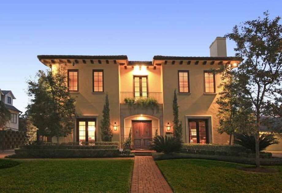 This spectacular Mediterranean-style home has a brick front walk and lush greenery. Photo: Keller Williams Realty