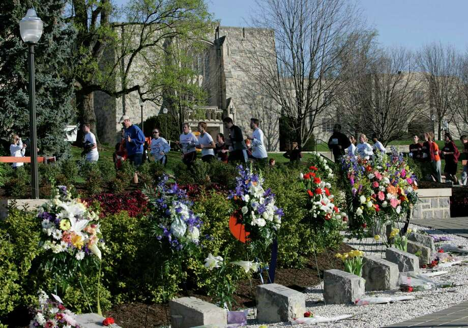 Runners pass the memorial for the 32 slain Virginia Tech students during a 3.2-mile run in honor of the victims of the April 16, 2007, shootings at Virginia Tech. A classroom building where a  student gunman killed 30 of the people is now home to the Center  for Peace Studies and Violence  Prevention. Photo: Steve Helber, AP / AP