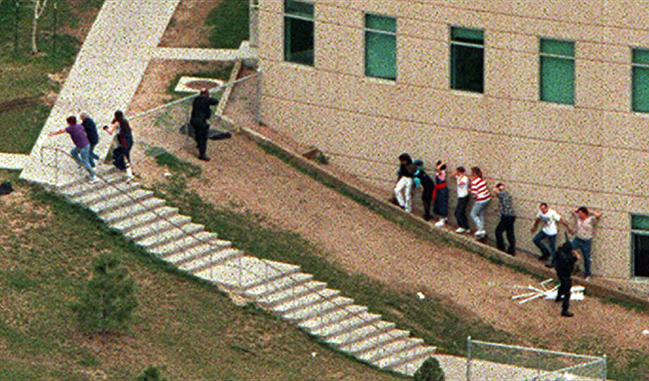 Police officers point weapons at a building as students take cover and flee the area outside Columbine High School in Littleton Colo., during a shooting rampage by two students on April 20, 1999. Eric Harris and Dylan Klebold killed 12 students and a teacher before taking their own lives.  Photo: RODOLFO GONZALEZ, AP / ROCKY MOUNTAIN NEWS