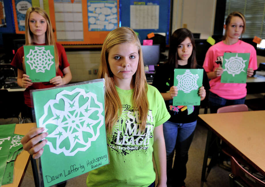From left, Skyler Authement, 13, Lexi Humphreys, 13, Rikki Hinojosa, 14, and Hanna Sadler, 14, of Little Cypress-Mauriceville Junior High cut out snowflakes in remembrance of the the 24 people that were killed in last week's Connecticut shooting. Each paper snowflake was created individually to commemorate the uniqueness of each individual Photo taken Monday, December 17, 2012 Guiseppe Barranco/The Enterprise Photo: Guiseppe Barranco, STAFF PHOTOGRAPHER / The Beaumont Enterprise