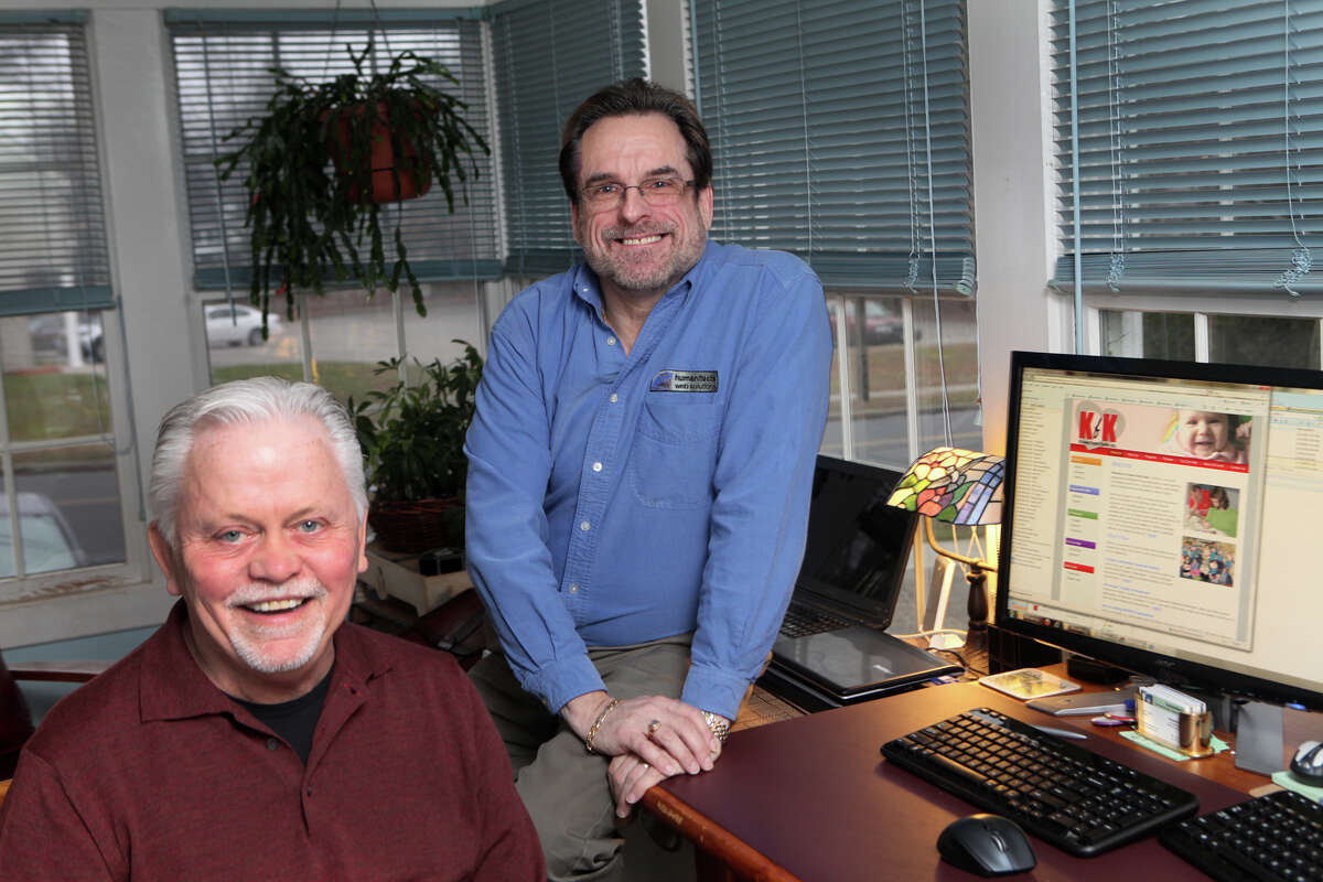 James Rude, president and founder of Humanitects, a web design company that specializes in helping nonprofit, health and human service sectors, right, sits with Gary Bunting, director of client services, in their Milford, Conn. home office on Monday, December 17, 2012.