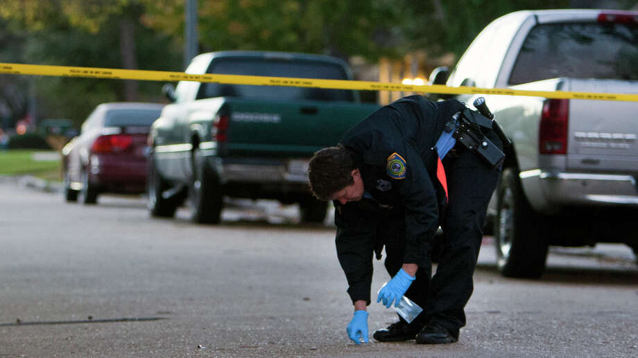 Police pick up bullet casings at a scene after a shooting took place in the 10400 block of Huntington Estates, Tuesday, Dec. 18, 2012, in Houston. Police said an altercation started between the suspects after a U-Haul truck showed up in front of a home with stolen goods. After the altercation started, a man fire shots from about a block away. There were no injuries, and the scene is under investigation. Photo: Cody Duty, Houston Chronicle / © 2012 Houston Chronicle
