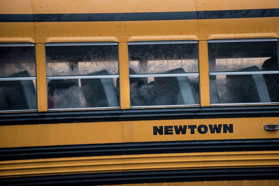 A school bus takes students to Newtown High School December 18, 2012 in Newtown, Connecticut. Students in Newtown, excluding Sandy Hook Elementary School, return to school for the first time since last Friday's shooting at Sandy Hook which took the live of 20 students and 6 adults.  AFP PHOTO/Brendan SMIALOWSKI Photo: BRENDAN SMIALOWSKI, AFP/Getty Images / 2012 AFP