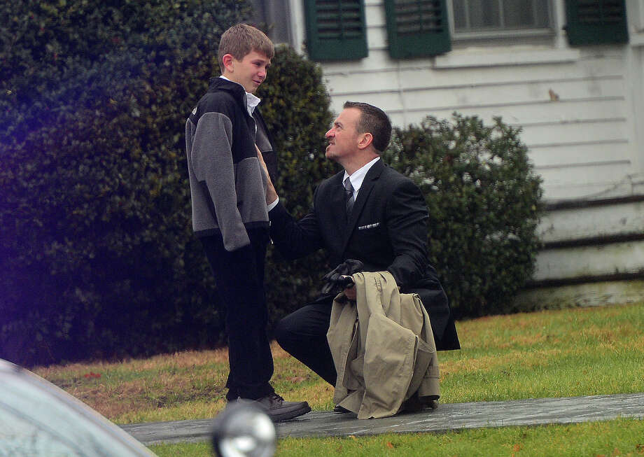 A man comfort a young mourner at Honan funeral while attending the funeral for Jack Pinto, 6, one of the victims of the Sandy Hook elementary school shooting, on December 17, 2012, in Newtown, Connecticut. Funerals began in the little Connecticut town of Newtown after the school massacre that took the lives of 20 small children and six staff, triggering new momentum for a change to America's gun culture. AFP PHOTO/Emmanuel DUNAND Photo: EMMANUEL DUNAND, AFP/Getty Images / 2012 AFP