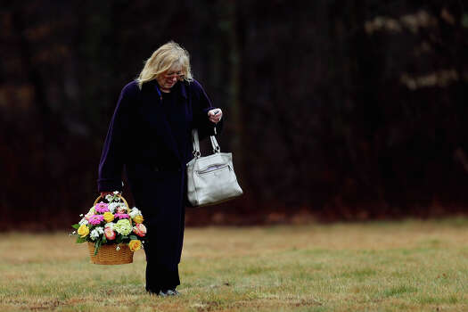 MONROE, CT - DECEMBER 17:  A woman carries a basket of flowers at the funeral services for six year-old Noah Pozner, who was  killed in the shooting massacre in Newtown, CT, at B'nai Israel Cemetery on December 17, 2012 in Monroe, Connecticut. Today is the first day of funerals for some of the twenty children and seven adults who were killed by 20-year-old Adam Lanza on December 14, 2012. Photo: Spencer Platt, Getty Images / 2012 Getty Images
